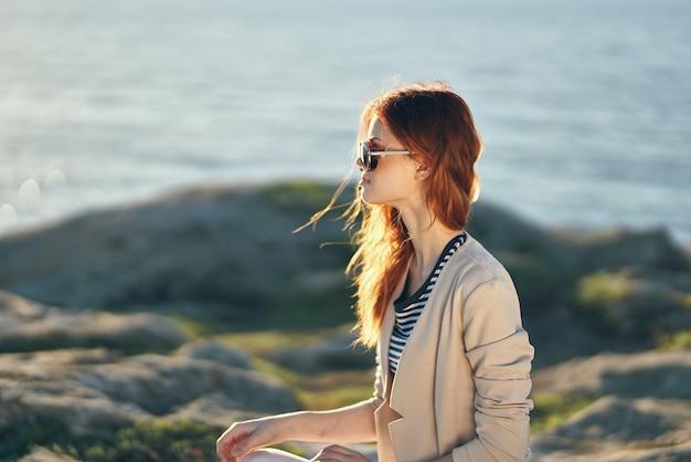 自然の風景の海の近くの山で眼鏡とセーターを着た女性