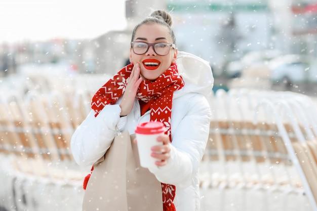 メガネと赤いセーターの女性はコーヒーを飲みながら通りにクローズアップ