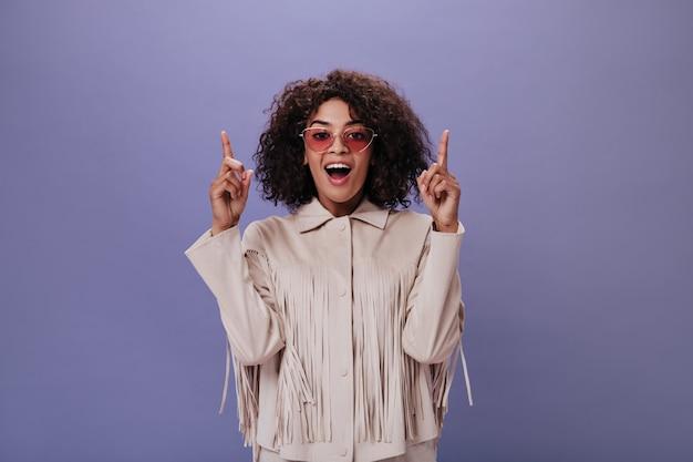 眼鏡をかけた女性が正面を見て、紫色の壁にテキストを配置するために指を上に向けます