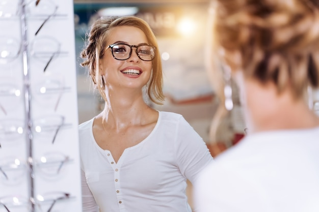 안경을 쓴 여자는 거울을 본다. 안경점. 광학 매장에서 여자입니다. 안과 가게. 확대.