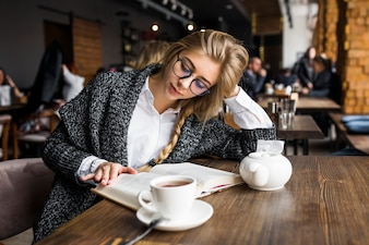 Woman in glasses reading book in cafe