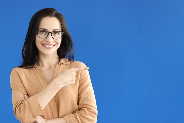青い背景の上の空のスペースに指を示す眼鏡の女性