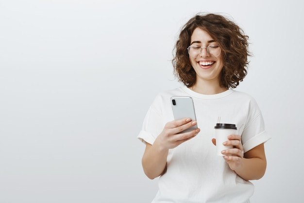 Женщина в очках, улыбаясь в текстовое сообщение мобильного телефона, пьет кофе во время перерыва в офисе
