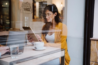 Woman in glasses using tablet in cafe