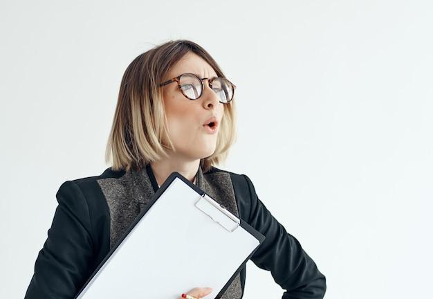 手にフォルダーを持つ眼鏡の女性空白シートスタジオオフィス