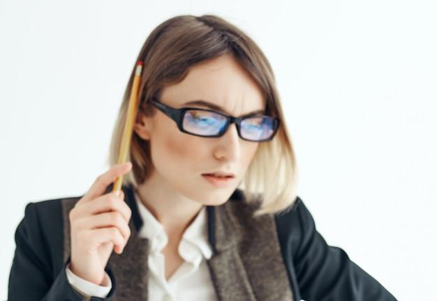 手のオフィスの明るい背景にメモ帳とメガネの女性