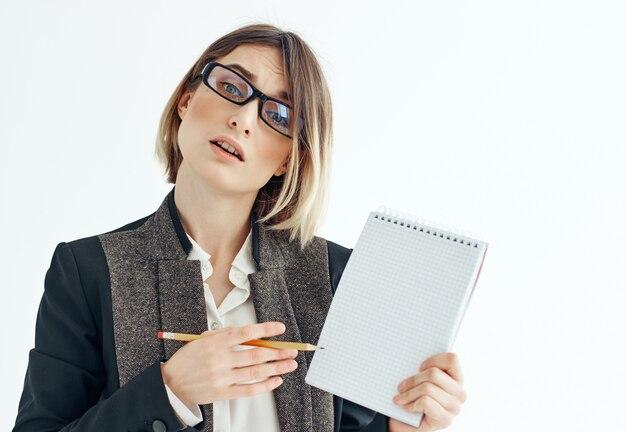 손 사무실 밝은 배경에 메모장이 있는 안경을 쓴 여자