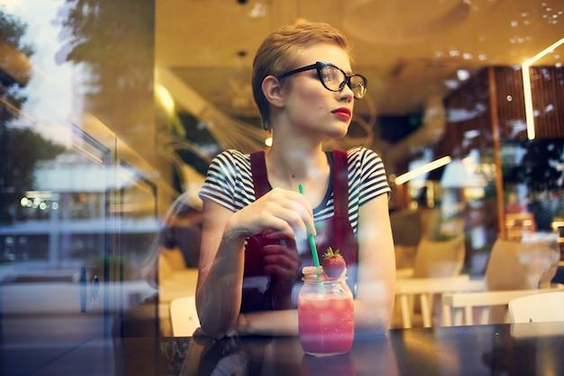 Женщина в очках с короткими волосами сидит в кафе одиночество, коктейль отдыхает