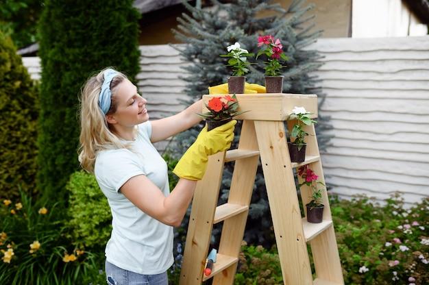 庭の鉢植えの花を育てる手袋の女性。女性の庭師は、屋外の植物、ガーデニングの趣味、花屋のライフスタイルとレジャーの世話をします