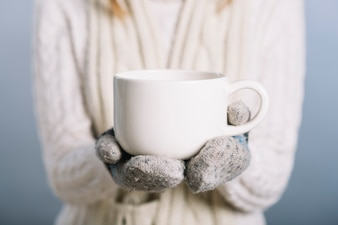 Woman in gloves holding cup