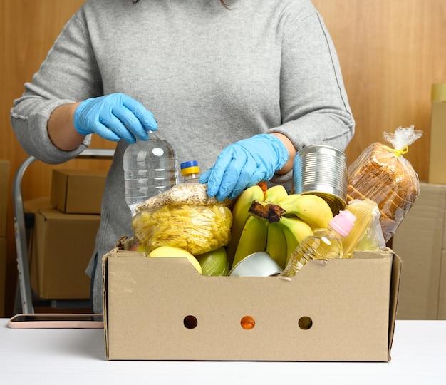 Женщина в перчатках продолжает собирать еду, фрукты и вещи, а также картонную коробку для помощи нуждающимся, концепция помощи и волонтерство. доставка продукции