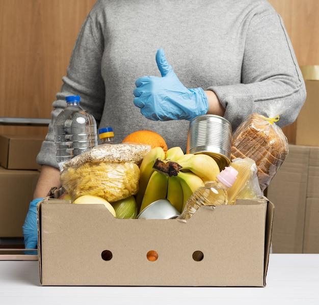 Женщина в перчатках продолжает собирать еду, фрукты и вещи, а также картонную коробку для помощи нуждающимся, концепция помощи и волонтерство.