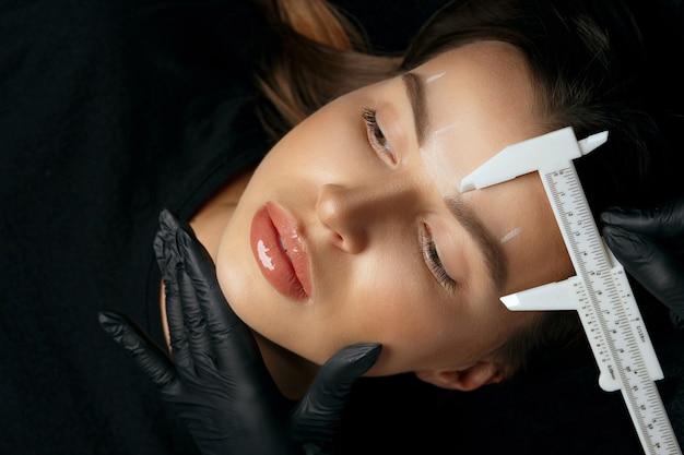 手袋をはめた女性は、美容院でゴージャスなブルネットの女性に永久的な眉メイクの前に測定を行います。上面図