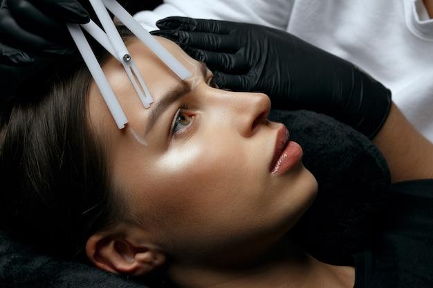 永久的な粉末染色の前に眉毛の測定を行う手袋の女性