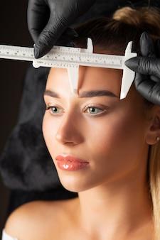 アートメイクの前に定規で眉を測定する手袋をした女性。クローズアップショット