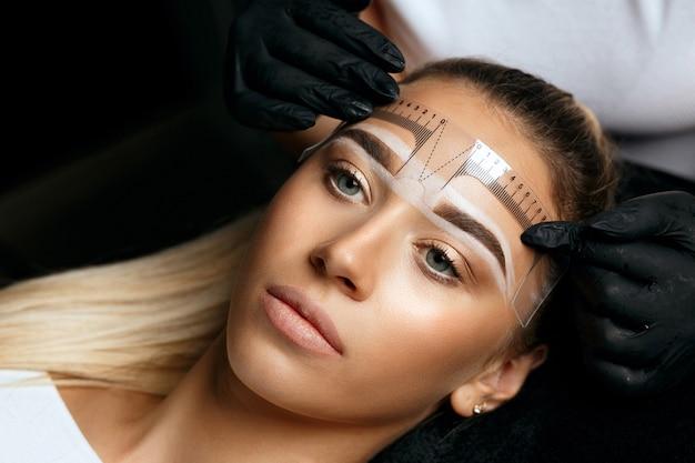 Женщина в перчатках измеряет линейкой и готовится нанести клиенту макияж бровей