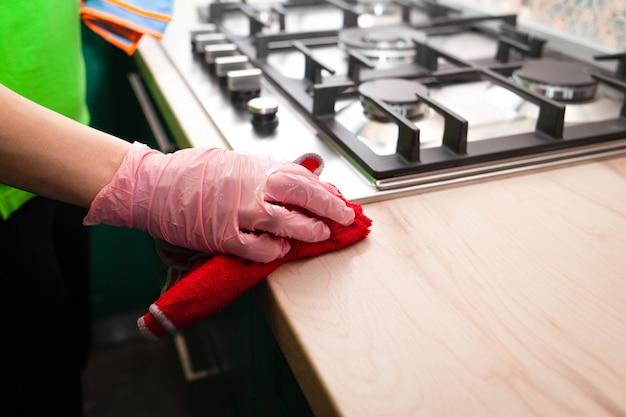 Женщина в перчатках вытирает мебель на кухне