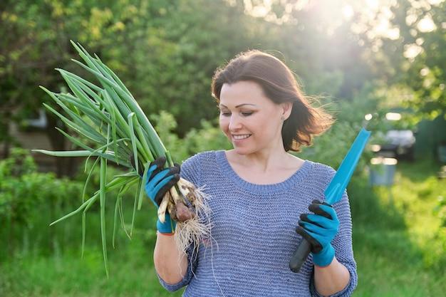 Женщина в перчатках с садовой лопатой держит букет свежего зеленого лука