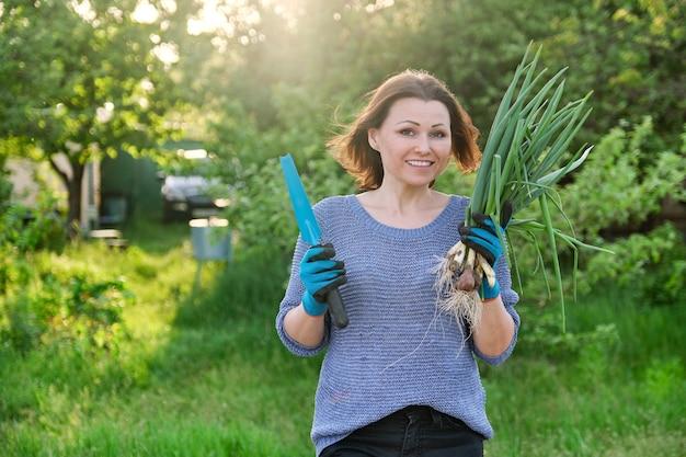 新鮮なネギの束を保持している庭のシャベルと手袋をはめて女性