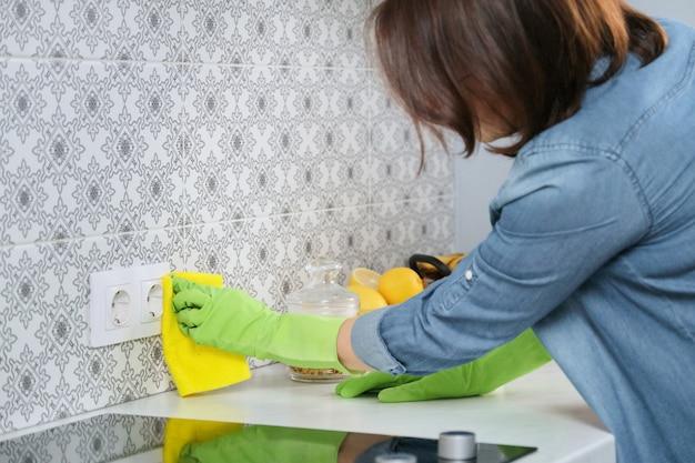 Женщина в перчатках с тряпкой убирает дом на кухне