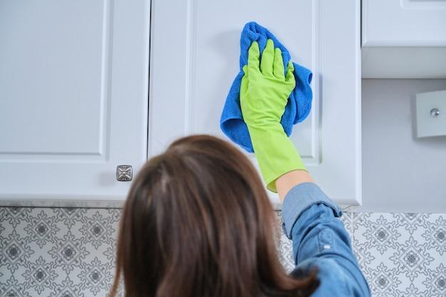 Женщина в перчатках с тряпкой для мытья, уборки, полировки мебельных дверей на кухне, уборки дома