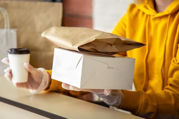 장갑을 낀 여성은 테이크아웃 주문으로 일합니다. 도시 covid 19 잠금, 코로나바이러스 폐쇄 동안 웨이터가 테이크아웃 식사를 제공합니다. 테이크 아웃 피자 커피, 음식 배달.