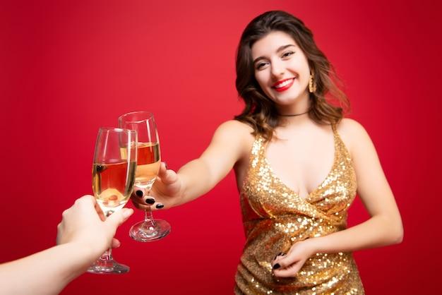 赤い口紅とシャンパンを手にゴールドのドレスを着た女性