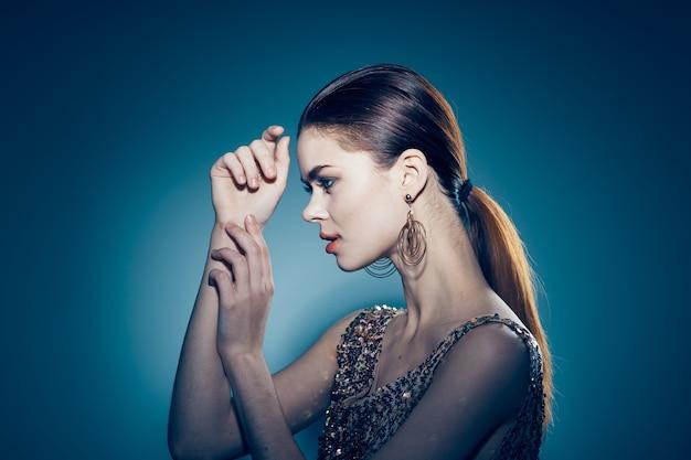 황금 드레스 장식 매력적인 포즈 스튜디오에서 여자
