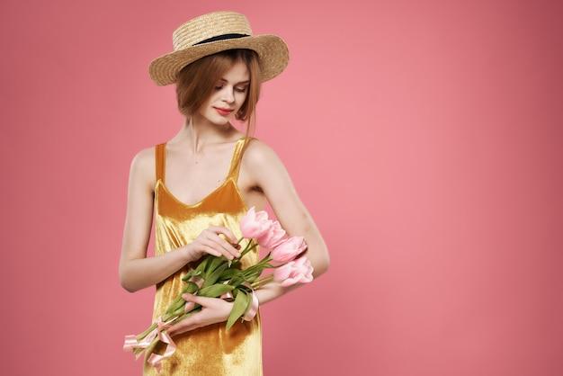 花の花束の装飾の魅力の孤立した背景を持つ黄金のドレスの女性。高品質の写真