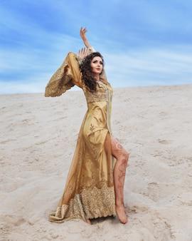 해변에서 황금 이브닝 드레스 여자