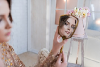 Woman in golden evening gawn and crown poses in luxury white room and looks in the mirror