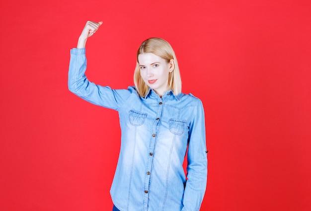 Женщина в хорошем настроении, поднимает руку с мышцами в синей рубашке