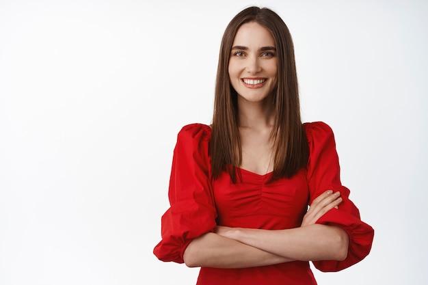 ゴージャスな赤いドレスを着た女性、自信を持って胸に腕を組んで、白い歯を笑顔で、白で決心しているように見える