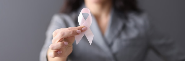 Женщина в сером деловом костюме, держа в руках розовую ленту, предотвращение рака груди крупным планом