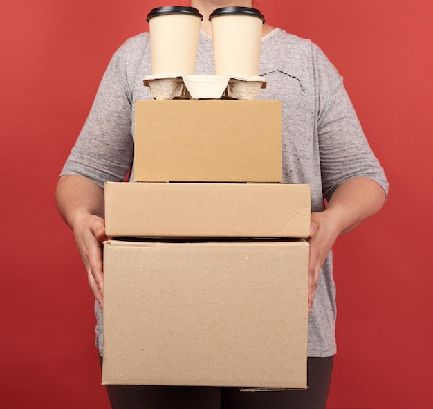 灰色の服を着た女性は、赤いスペースに茶色の紙箱とコーヒーと使い捨てメガネのスタックを保持し、オンライン注文配信の概念