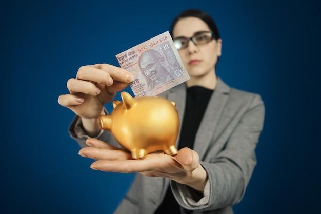 Женщина в сером пиджаке с индийской рупией и копилкой в руках.