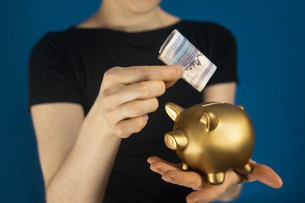 Женщина в сером пиджаке с российскими деньгами и копилкой в руках.