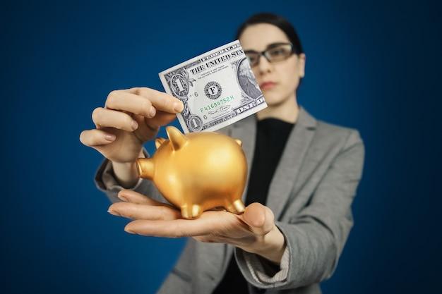 Женщина в серой куртке с долларом usd и копилкой в руках.