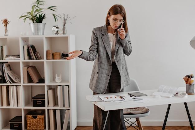 비즈니스 파트너와 전화 통화하는 회색 양복에 여자. 차트를 보면 성인 숙 녀의 초상화입니다.