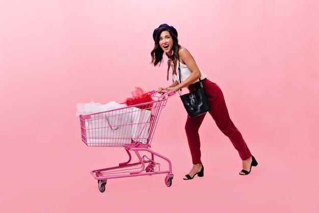 気分のいい女性が笑ってスーパーからトロリーを運転しています。ピンクの背景に黒いベレー帽の笑顔とブルゴーニュのズボンの女の子。