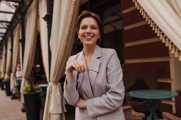カメラを見て、レストランの近くでポーズをとる素晴らしい気分の女性。灰色の特大ジャケットの陽気な女の子は心から外で微笑む