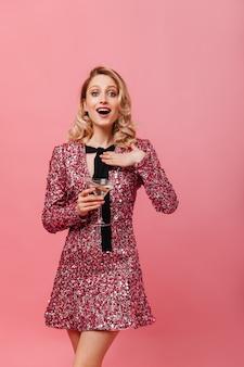 ピンクの壁にポーズをとって、気分がいい女性