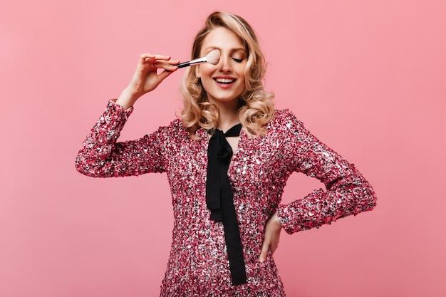 ピンクの壁に化粧ブラシでポーズをとって素晴らしい気分の女性