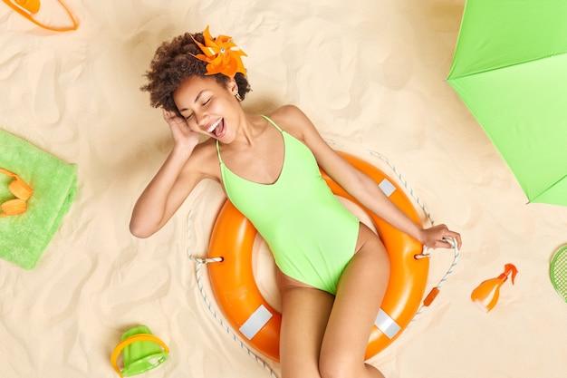 緑のビキニを着た女性が膨らんだ救命浮輪にポーズをとって口を開けたまま目を閉じて夏のようなビーチで自由な時間を過ごします。人々の休日のリラクゼーションの概念
