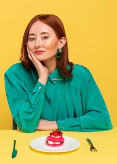 Женщина в зеленой блузке сидит рядом с вкусным тортом