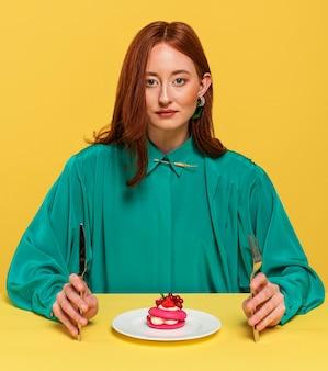 おいしいケーキの横に座っている緑のブラウスの女性