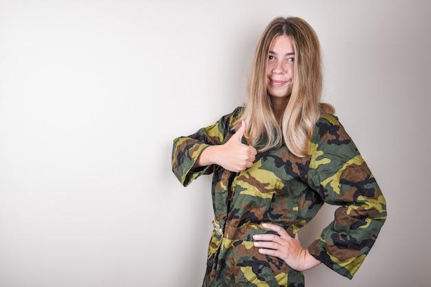 親指を上に表示している緑のカモフラージュローブの女性。軍の概念。