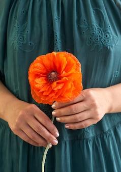 Женщина в зеленом платье с цветами poppe, крупным планом на руках. весенние сны.