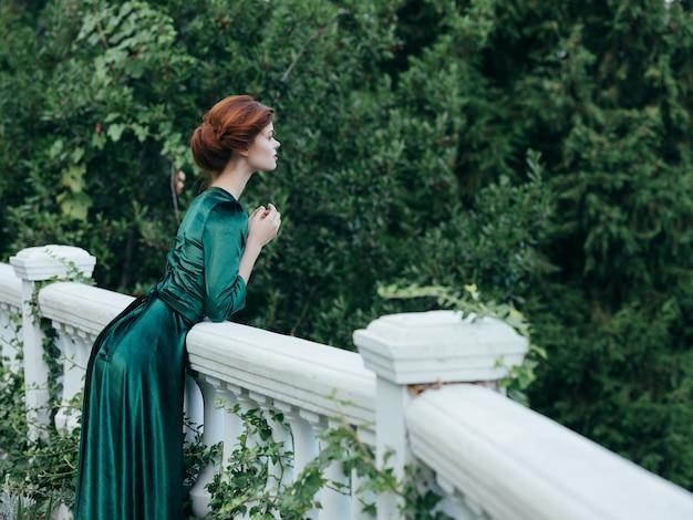 公園の自然の贅沢なロマンスの緑のドレスの女性