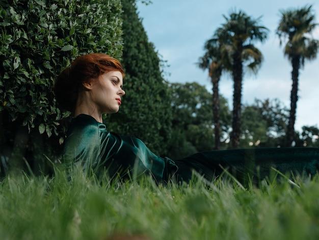 Женщина в зеленом платье лежит на траве природы и роскошной модели животного.